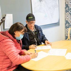 Marjatta ja Osmo Autio ostavat tonttia Lapuan kaupungin työntekijöiden Anne Jäätteenmäen ja Markku Turjan valvovan silmän alla.