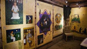 Suurikokoisia julisteita, jossa värikkäitä kuvia noitavainoista, nainen itsumassa metsässä, rovio, hirttopuu yms.