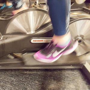 Hjulen på en motionscykel som är igång med en fot på pedalen.