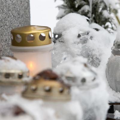 Hautakynttilöitä lumisessa maisemassa hautausmaalla