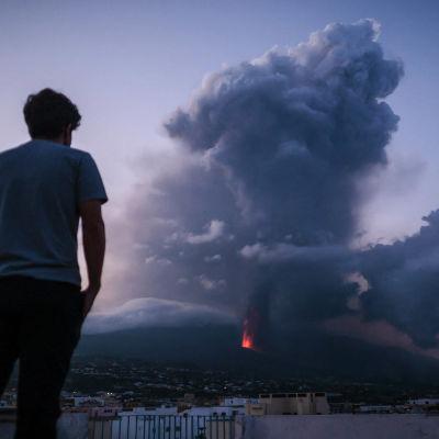 Henkilö katselee kohti tulenvuoren purkausta iltahämärällä.