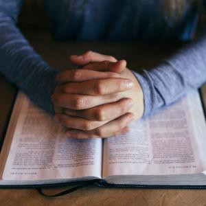 Kuvassa on ristityt kädet kirjan (ehkä raamatun) päällä.