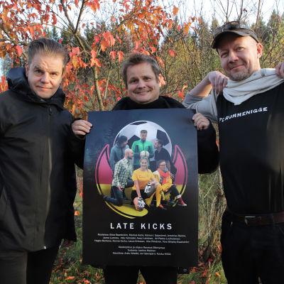 Kolme miestä poseeraa kameralle elokuvajulistetta esitellen