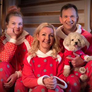Månssonin perhe joulupyjamissaan kodin portailla.
