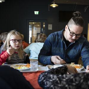 Lapsi ja aikuinen syömässä kouluruokalassa.
