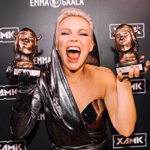 Anna Puu pitelee kahta voittamaansa Emma-palkintoa molemmin puolin kasvojaan ja hymyilee leveästi silmät kiinni.