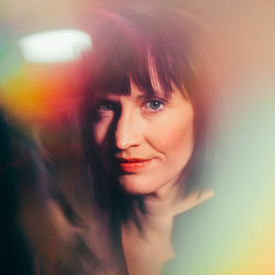 Maija Vilkkumaa katsoo kameraan heijastuksen keskeltä.