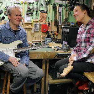 Mies ja nainen istuvat soitinrakennuspajassa, toisella sylissään sähkökitara, toisella ukulele.