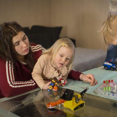 Nainen ja kaksi lasta pelaamassa Kimbleä.