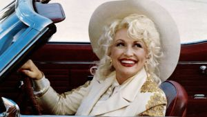 Dolly Parton i cowboyhatt sitter i öppen bil