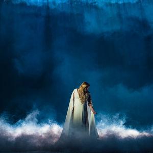 UMK-finalisti Catharina Zühlke seisoo lavalla valkoisessa mekossa valkoisen savun saartamana. Kuvan tausta on syvänmeren sininen.