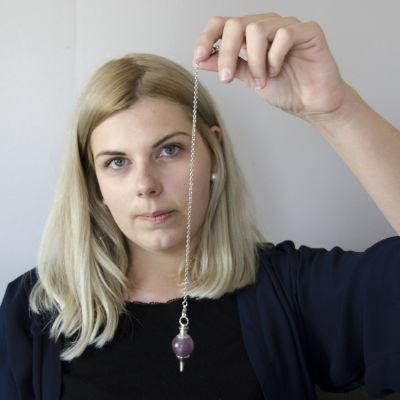 Hypnoterapeut Michelle Ferm håller i en pendel.
