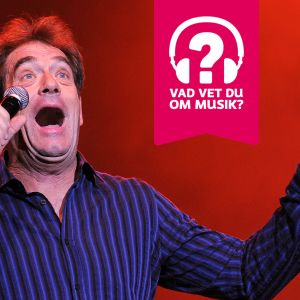 Huey Lewis sjunger i en mikrofon.