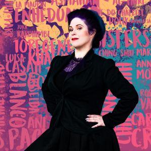 Nainen (Maria Pettersson) poseeraa 1900-luvun tyylisessä asussa värikkään taustan edessä.