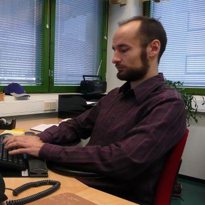 Oikeusavustaja Tommi Hoikkala työpöydän äärellä