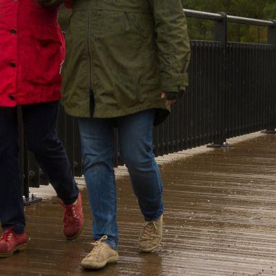 Kaksi naista kävelee sateessa sillalla.