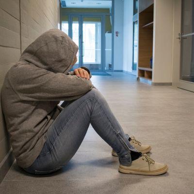 Huppariin kääriytynyt anonyymi nuori istuu koulun käytävällä.