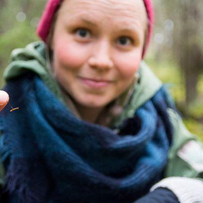 Nainen pitää metsässä kädessään pientä sientä.