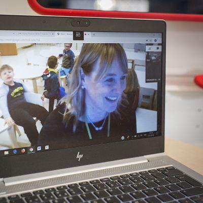 Ihmisiä kannettavan tietokoneen näytöllä.