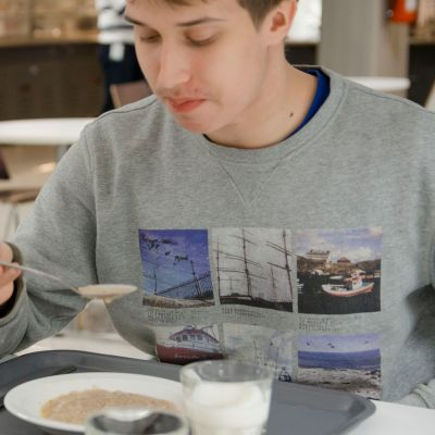Opiskelija syö puuroa koulun ruokalassa.