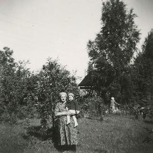Vanhempi nainen nuori tyttö sylissään 1950-luvulla kaupunkipuutarhassa.