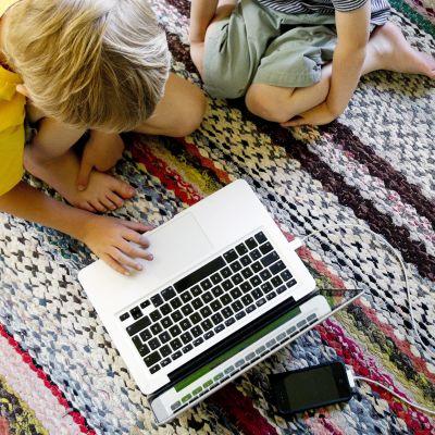 Kaksi pientä poikaa kannettavan tietokoneen äärellä.