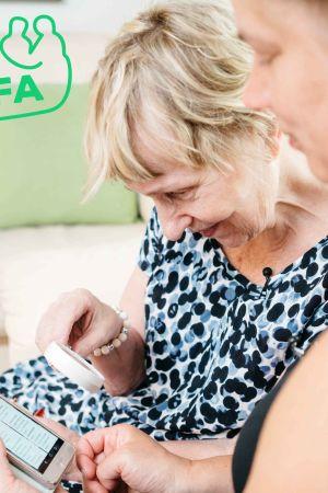 Äldre kvinna lära sig använda en mobiltelefeon.