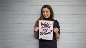 """Sarah Jussila från Fashion Revolution håller upp en skylt där det står """"Who made my clothes?"""""""