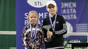 En flicka och en pojke som har fått en tennispokal