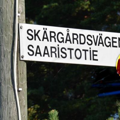 Skylt med texten Skärgårdsvägen och en gul cykel.