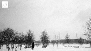 En man går på en stig i snön
