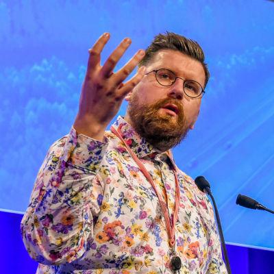 Sebastian Tynkkynen står och talar på Sannfinländarnas årsmöte 2021.