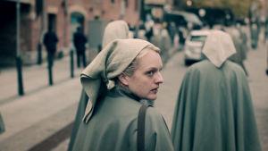 Elisabeth Mossin hahmo June kävelee kadulla katsoen taaksepäin, martan asu yllään.
