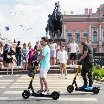 Potkulautailijoita ja jalankulkijoita kadulla pietarissa.
