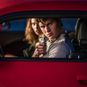 Baby (Ansel Elgort) och Debora (Lily James) sitter i en bil och Baby siktar med en pistol ut genom bilfönstret.