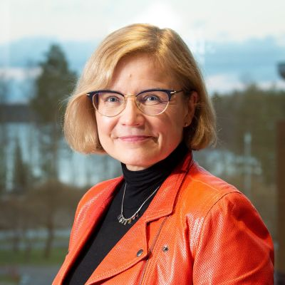 en medelålders kvinna i lederjacka och glasögon som ler mot kameran