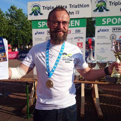 Marko Forsell tripla-triathlonin palkintojen jaossa käsi siteessä standin kaaduttua hänen päälleen.