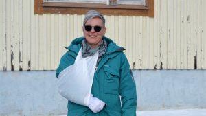 Porträttfoto av kvinna med grönblå jacka, svarta solglasögon, ena armen i mitella. Hon tittar in i kameran och ler stort. Bakom en träbyggnad som är beigemålad.