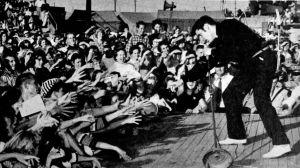 Elvis Presley på scenen år 1956 inför en skrikande pubilk som sträcker ut armarna mot honom.
