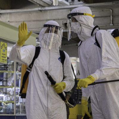 Personer i skyddsutrustning går på ett flygfält i Brasilien.