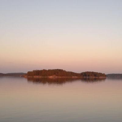 Sen kväll i Åbolands skärgård, med ett rosa sken över öar och hav.