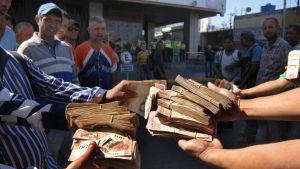 Folk med buntar av sedlar på 100 bolivar i staden Maracaibo i Venezuela.