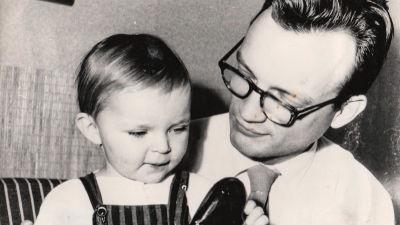 Annika som barn sitter i sin pappas famn. Bilden är svartvit.