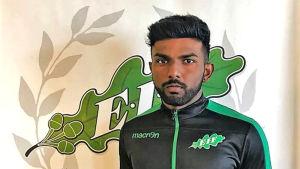 En ung fotbollsspelare i svartgrön EIF-blus står framför EIF:s logo som finns på väggen.