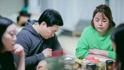 Eun-mi och hennes familj kring köksbordet i höghuset där de bor.