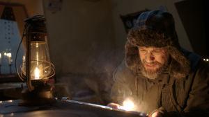 Petter i tjock skinnmössa försöker läsa i skenet från en oljelampa och en tändare.