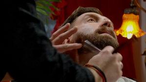 En mans hals blir rakad med rakkniv.
