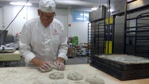 En man bakar rågbröd i ett bageri.