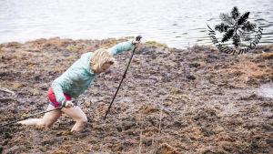 Kristiina Komulainen juoksee suossa sauvojen kanssa.