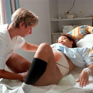 Gravid kvinna ligger i en sjukhussäng och föder barn. En barnmorska hjälper henne.